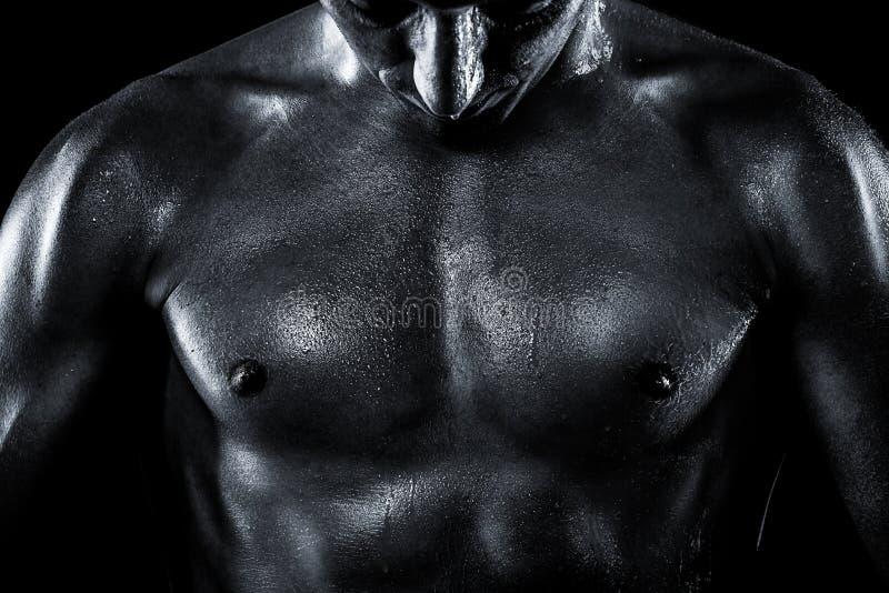 Schwitzendes Teil der Mannkarosserie auf einem schwarzen backgro lizenzfreie stockfotografie