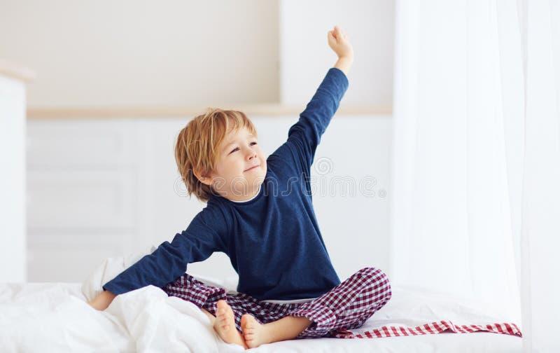 Schwungvoller Junge, der morgens aufwacht stockbild