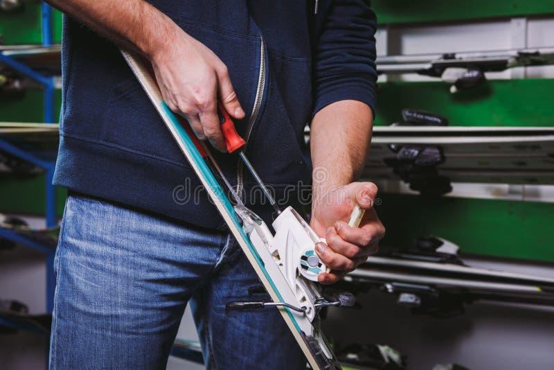 Sci dell'attrezzatura dello sci di tintura e di riparazione di tema Primo piano di un uso caucasico della mano del ` s dell'uomo  fotografie stock