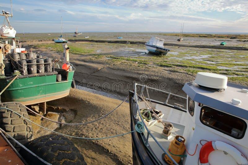 Sciabiche da pesca variopinte attraccate alla banchina con la spiaggia fangosa a bassa marea nei precedenti, Leigh sul mare fotografia stock