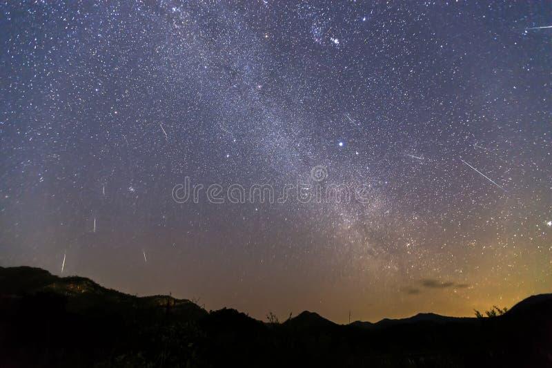 Sciame meteorico di Geminid e la Via Lattea sopra una montagna Meteora di Geminid nel cielo notturno immagine stock