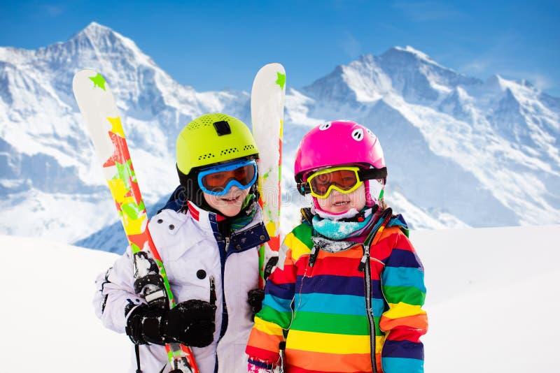 Sciare e neve divertenti per i bambini sulle montagne d'inverno immagine stock