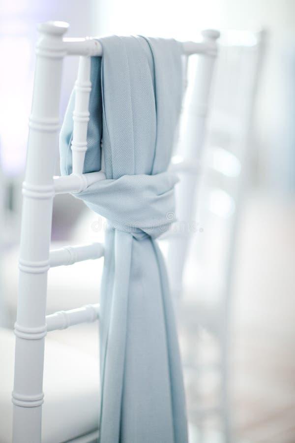 Sciarpa blu sulla sedia bianca di nozze - messa a fuoco sulla sciarpa fotografia stock libera da diritti