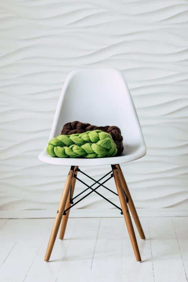Sciarpe tricottate variopinte della lana merino sulla sedia bianca fotografie stock libere da diritti