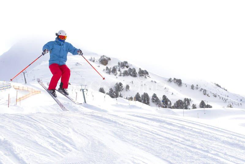 Sciatore con occhiali da sci arancioni nel casco bianco per gettare la pista da sci sulla cima delle montagne delle Alpi Sullo sf fotografie stock