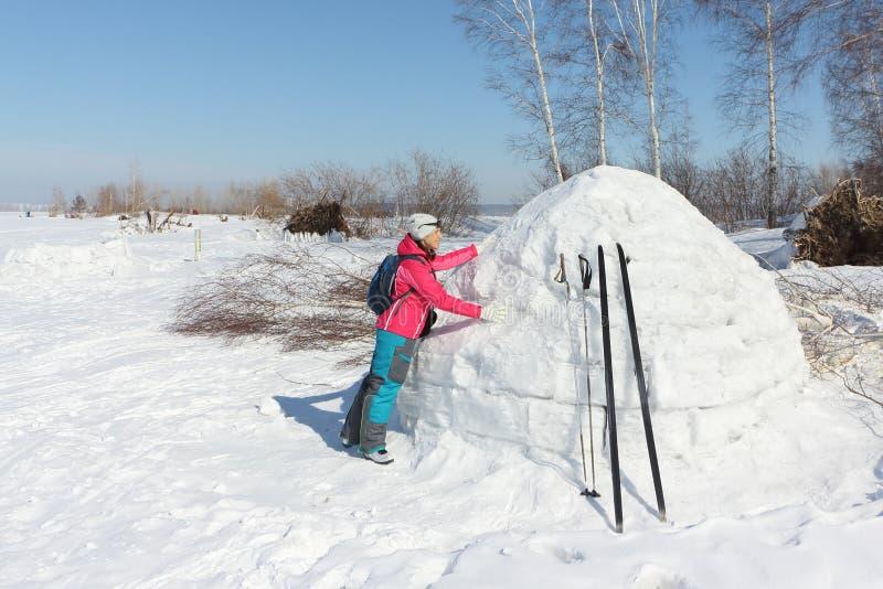Sciatore felice della donna in un rivestimento rosso che sta vicino ad un iglù immagine stock