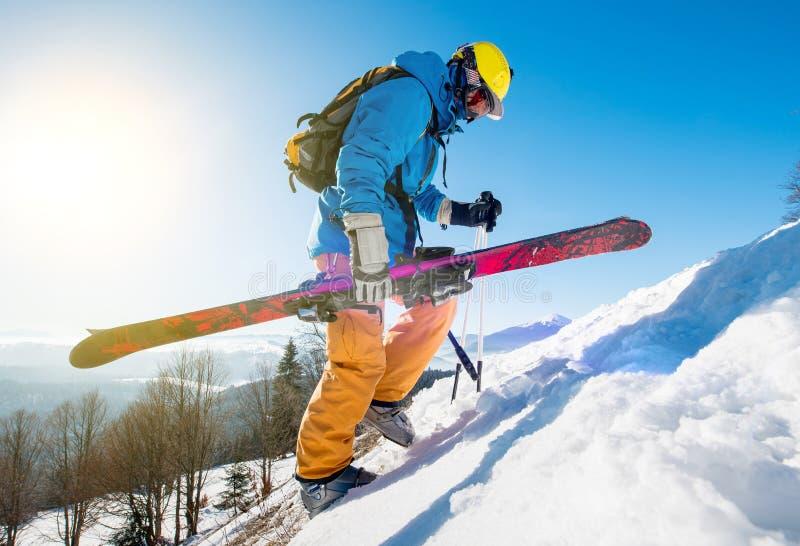 Sciatore maschio che cammina sulla collina nevosa nelle montagne di Carpathians che portano i suoi sci immagine stock libera da diritti