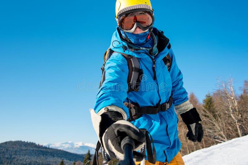 Sciatore maschio che per mezzo del bastone del selfie che prende le foto mentre sciando fotografia stock