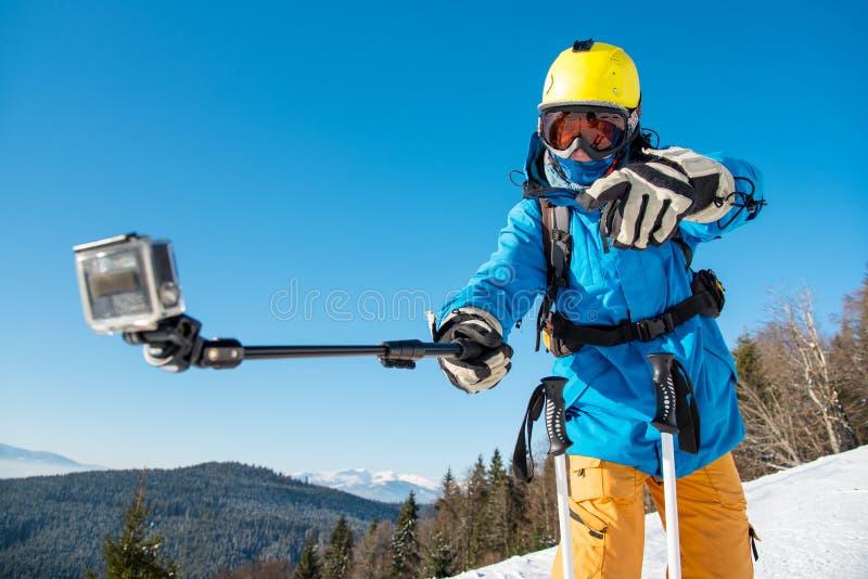 Sciatore maschio che per mezzo del bastone del selfie che prende le foto mentre sciando fotografie stock