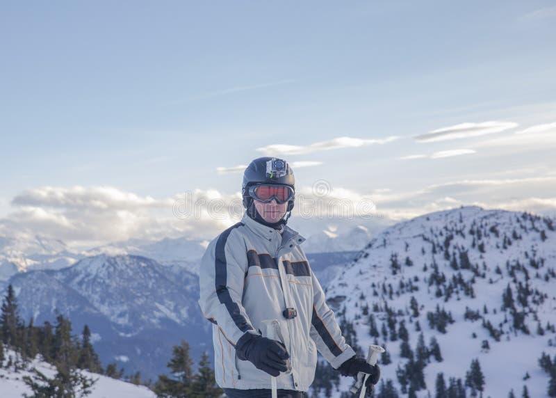 Sciatore maschio europeo che usando la macchina fotografica di azione sopra la montagna fotografia stock
