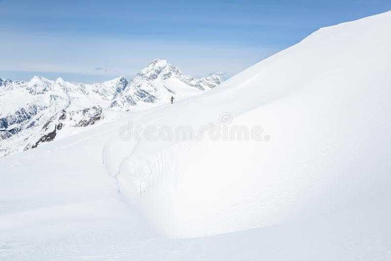 Sciatore nella distanza attraverso il grande cornicione di neve windblown Sopra lui è il supporto Sir Donald in Glacier National  fotografia stock libera da diritti