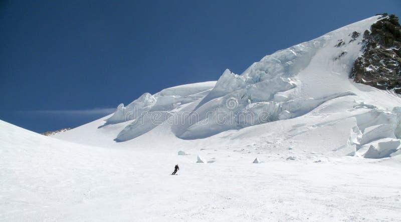 Sciatore remoto che scia giù un ghiacciaio alpino enorme un bello giorno di inverno con i seracchi d'attaccatura del ghiaccio die fotografia stock libera da diritti