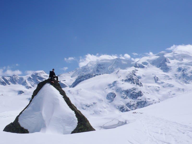 Sciatore remoto che si siede sopra una grande roccia innevata in mezzo di paesaggio spettacolare della montagna di inverno immagine stock