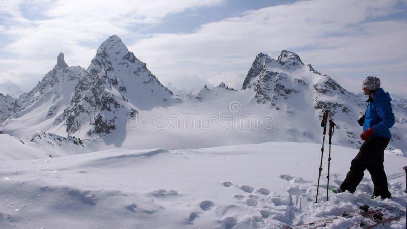 Sciatore remoto maschio sopra una sommità alpina a distanza che ammira la vista fantastica del paesaggio della montagna lui fotografia stock libera da diritti