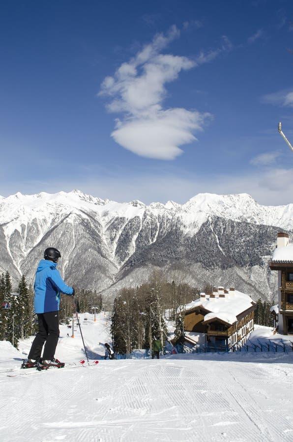Sciatore sulla cima del pendio su una stazione sciistica Laura Russia delle montagne di Caucaso di giorno soleggiato immagine stock