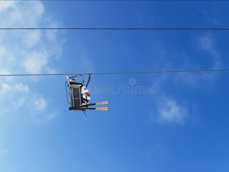 Sciatori che guidano nelle sedie sulla collina sulla cabina di funivia fotografia stock libera da diritti