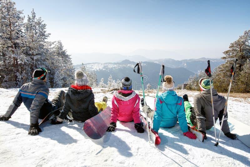 Sciatori che si siedono sulla neve e che guardano paesaggio, vista posteriore fotografia stock