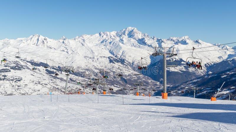 Sciatori nella La Plagne della stazione sciistica che si siede sulle seggiovie un giorno soleggiato Montagna di Mont Blanc nel fo fotografie stock