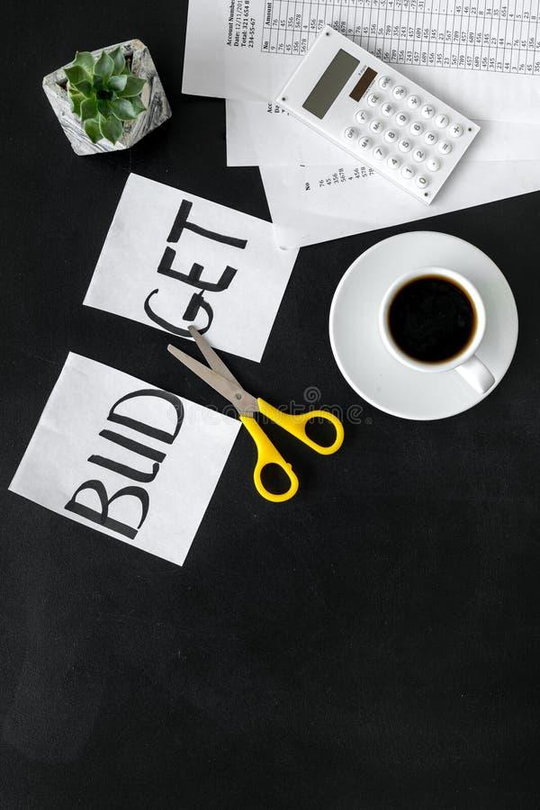 Sciccors et papier avec le budget de mot, le café et le plan pour le budget réduisant sur la maquette noire de vue supérieure de  images libres de droits