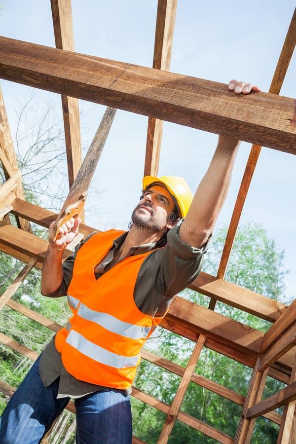 Scie à main de Cutting Wood With de travailleur de la construction à photos libres de droits