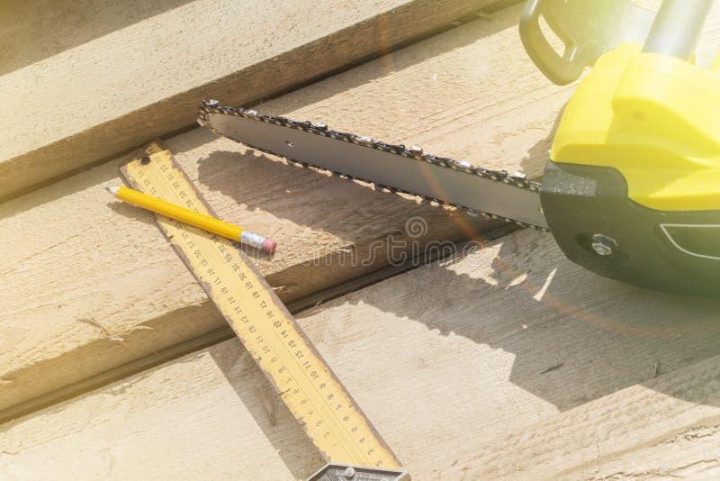 Scie, crayon et une ligne carrée sur les combles Construction des maisons et des toits en bois photos stock
