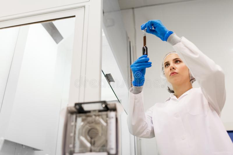 Woman with sulphuric acid in dropper at laboratory stock photography