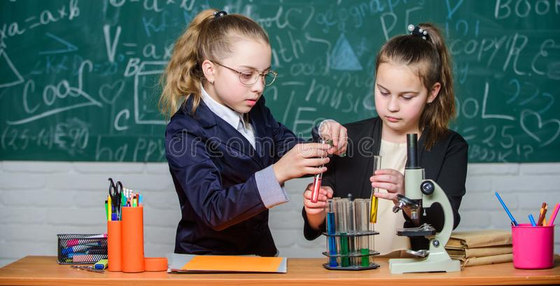 Science experiments in laboratory. Chemistry research. Little girls in school lab. Formal school education. Little. Scientist work with microscope. Biology royalty free stock image