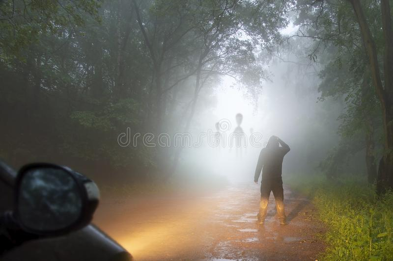 A science fiction concept of a man looking at aliens coming out the mist on a foggy, spooky forest road in the evening. Highlighte royalty free stock photo