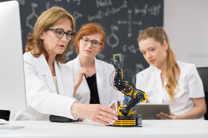 Science starts from the observation. Young students looking at the experiment with a robot royalty free stock photos