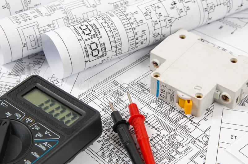 Science, technology and electronics. Electrical engineering drawings printing with circuit breaker and mulyimeter. Scientific deve stock images