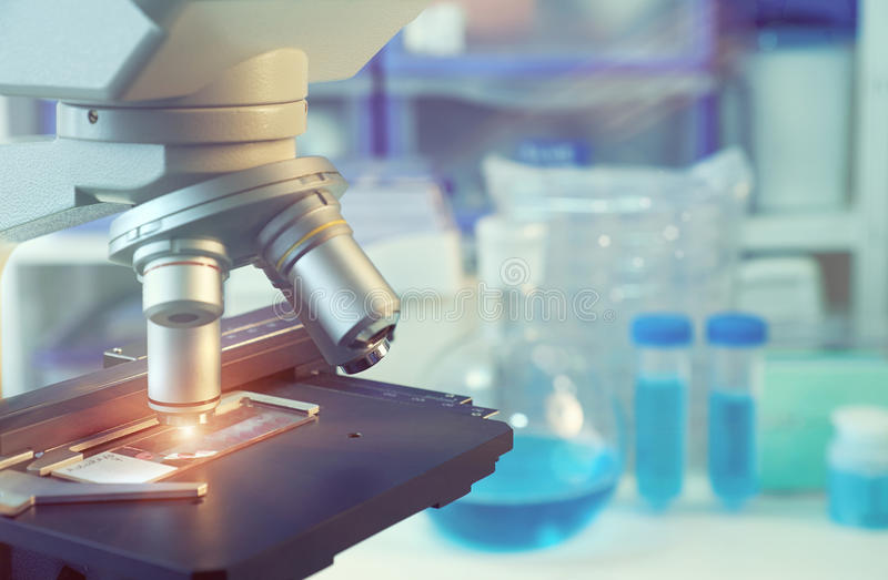 Scientific background with closeup on light microscope and blurred laboratory. Scientific background with closeup on light microscope and laboratory out of focus royalty free stock photography