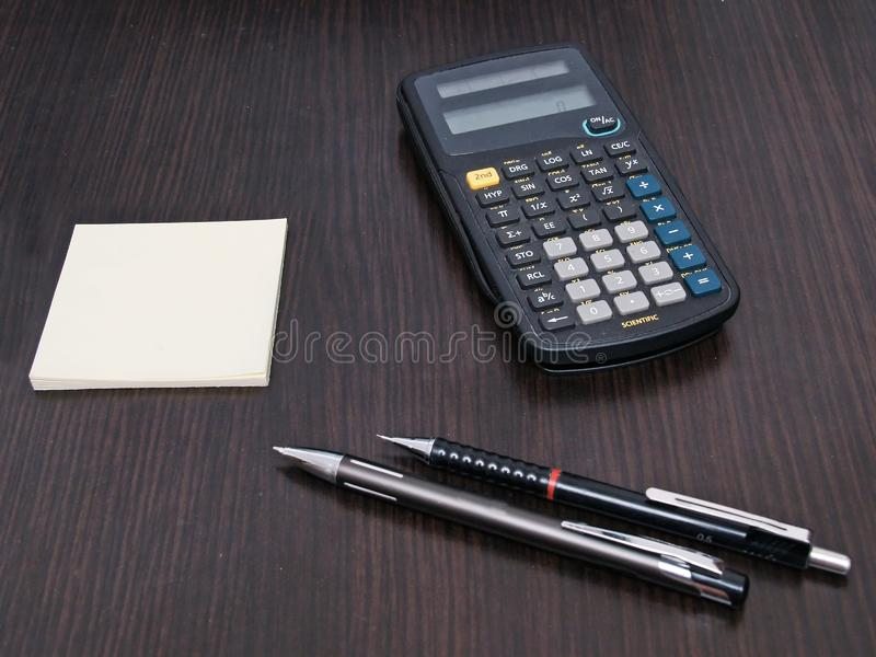Scientific calculator pencil pen and block notes on desktop stock image