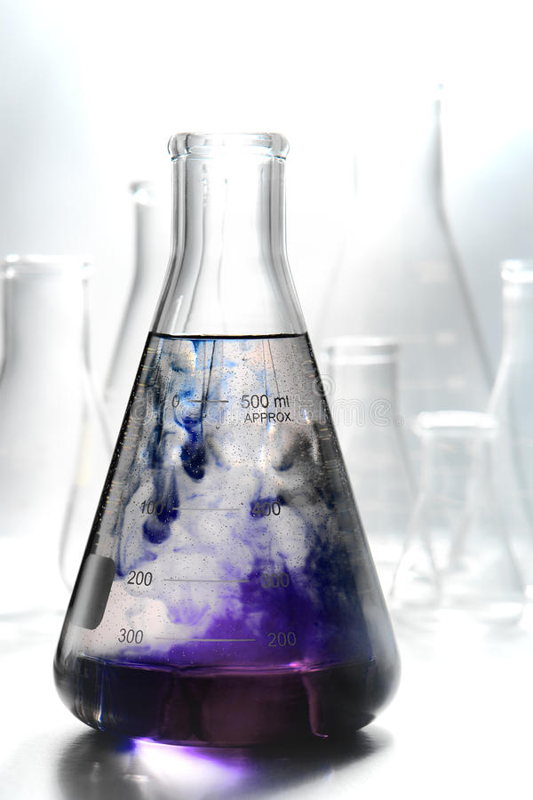 Scientific Experiment in Science Research Lab. Scientific laboratory glass conical Erlenmeyer flask filled with swirling and reacting purple chemical liquid mix stock images