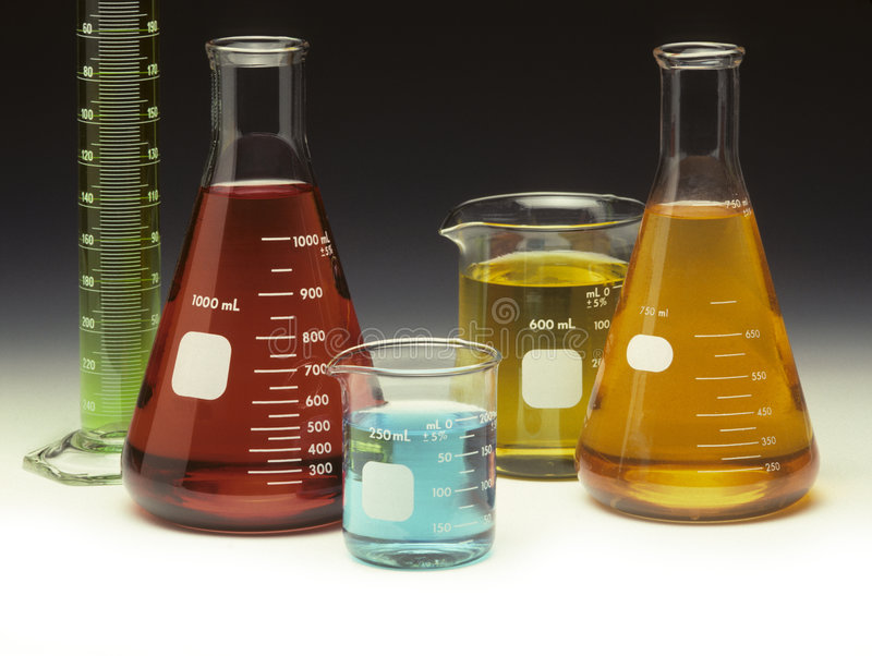 Scientific glassware filled with colored liquids. On a graduated background royalty free stock image