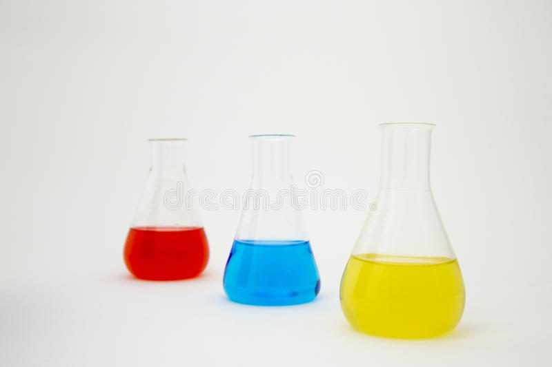 Scientific laboratory glass erlenmeyer flask filled with blue, yellow and red liquid on white background.  stock photos