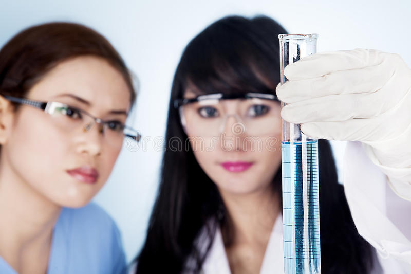 Scientific research team looking at clear solution. Female scientific research team holding a clear blue solution inside a flask in laboratory stock photo