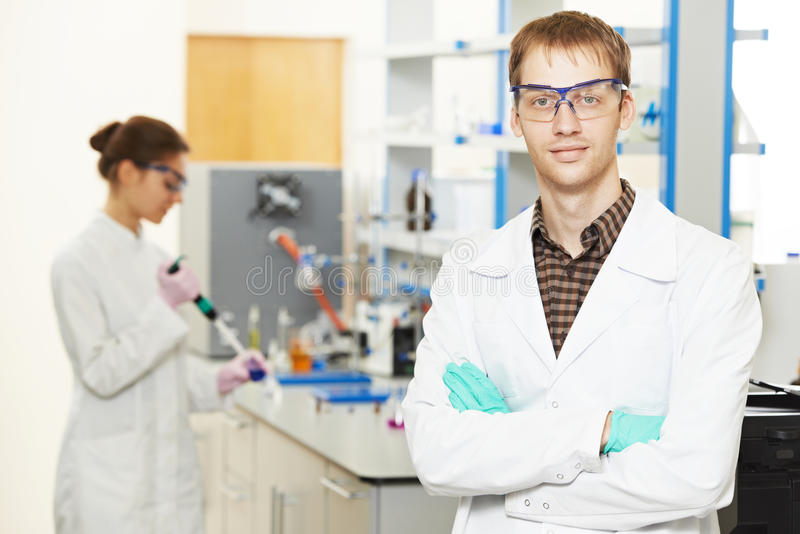 Scientific researchers making experiment in laboratory. Pharmacy and chemistry theme. Portrait of male scientific researcher in front of female lb worker making royalty free stock image