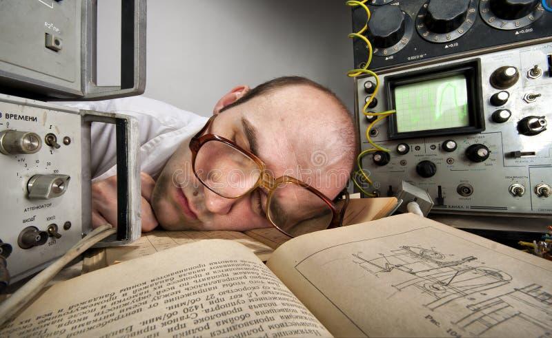 Scientifique épuisé dormant sur le livre photographie stock libre de droits