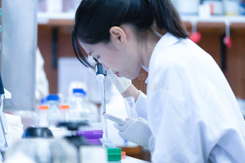 Scientifique asiatique de femmes avec faire la recherche dans le laboratoire clinique images stock