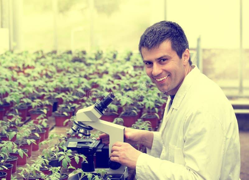 Scientifique avec le microscope dans la maison verte photographie stock