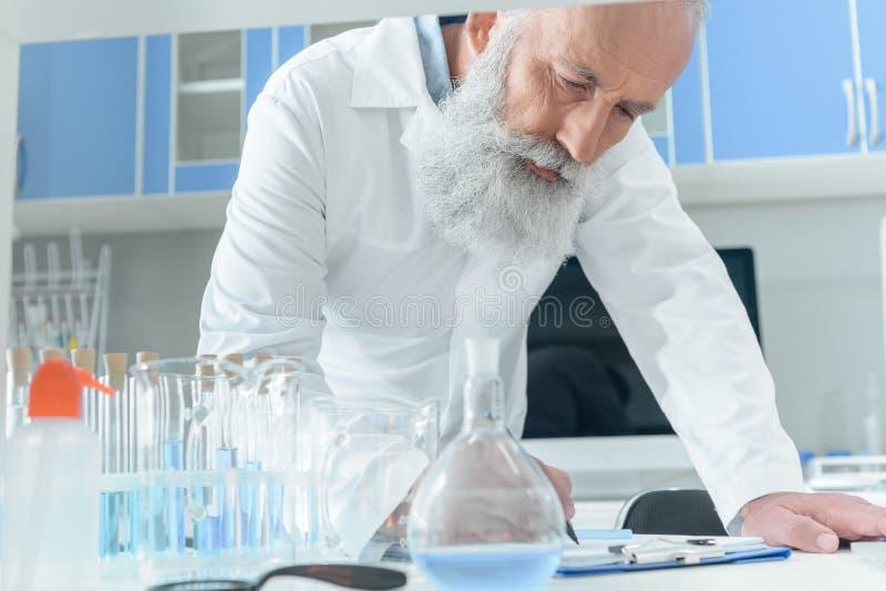Scientifique barbu supérieur dans l'écriture blanche de manteau dans le presse-papiers sur le tanle avec des flacons dans le labo photographie stock