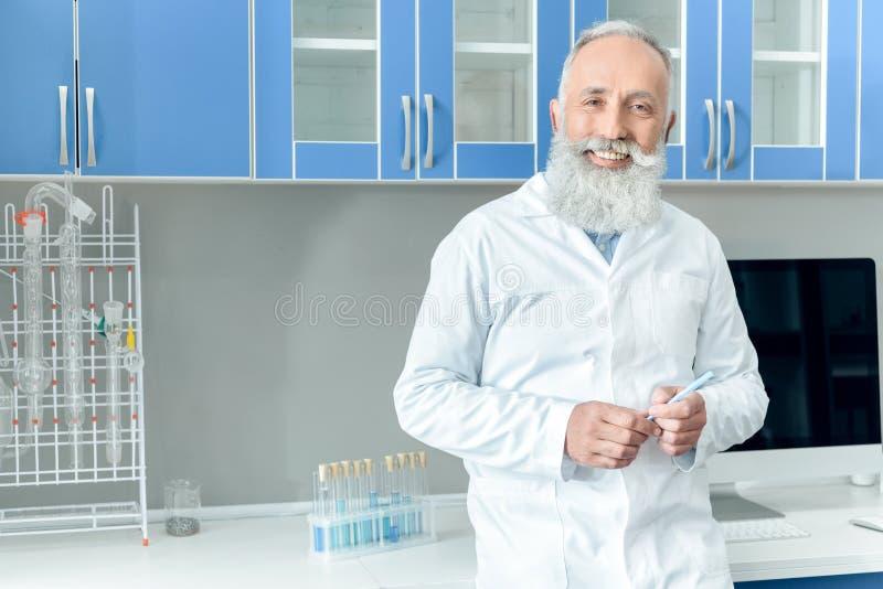 Scientifique barbu supérieur dans le manteau blanc tenant le tube avec du réactif dans le laboratoire chimique images stock