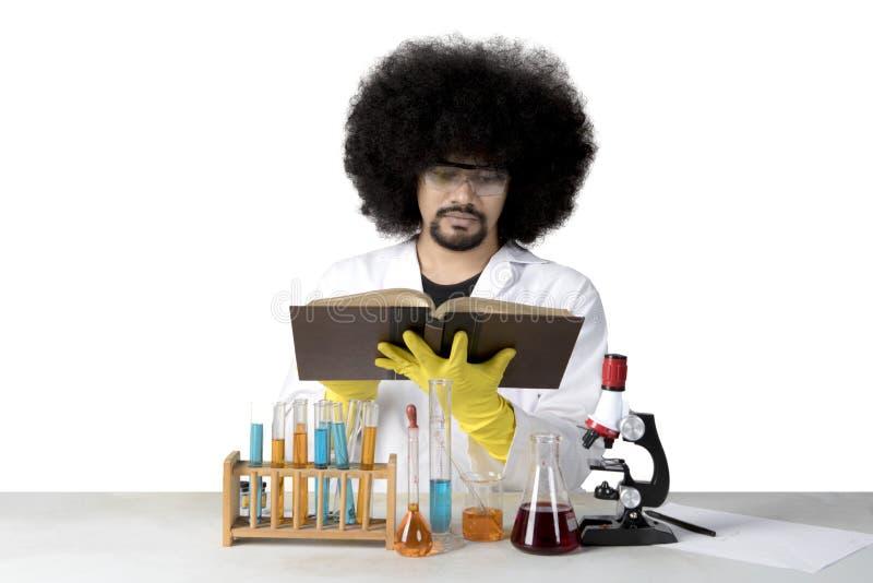 Scientifique d'Afro lisant un livre sur le studio photographie stock libre de droits