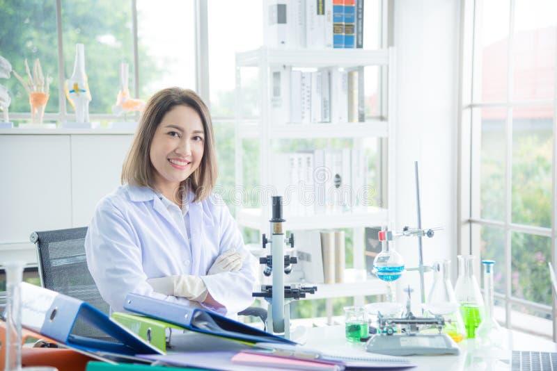 Scientifique dans le manteau blanc se reposant dans le laboratoire et le sourire à la caméra photographie stock libre de droits
