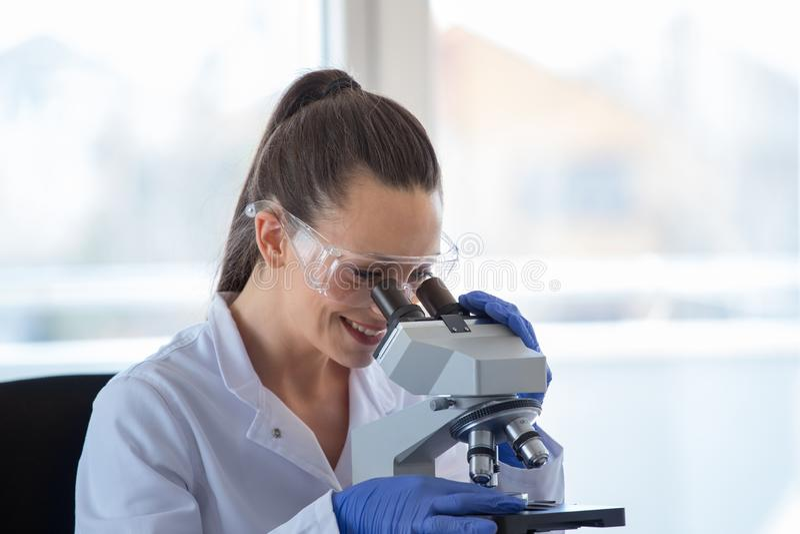 Scientifique de femme avec le microscope photographie stock