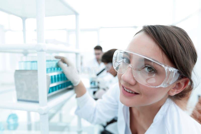 Scientifique de jeune femme en verres protecteurs tenant des tubes à essai photos stock