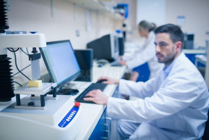 Scientifique de nourriture employant la technologie pour analyser le fromage image stock