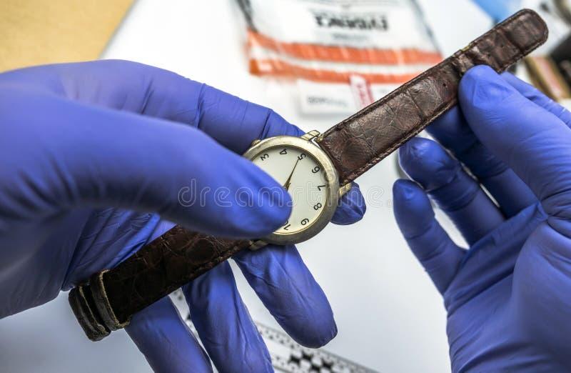 Scientifique de police travaillant dans le laboratoire criminalistique, analyse d'horloge de victime pour le meurtre photo stock