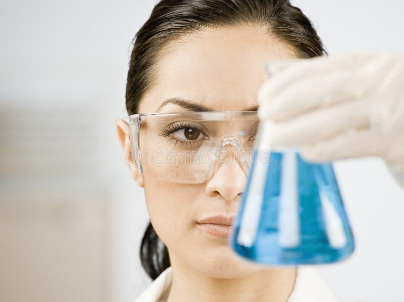 Scientifique féminin regardant le becher de liquide photographie stock