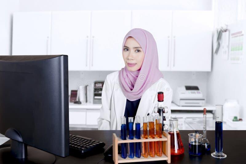 Scientifique féminin s'asseyant et souriant dans le laboratoire photos libres de droits